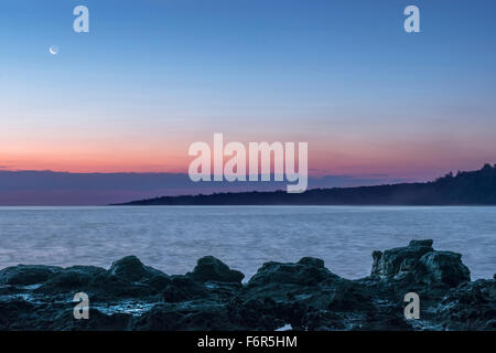 Sunrise over rock formations on beach - Stock Photo