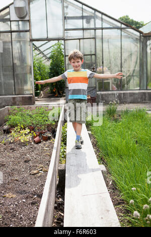 Boy playing in front of greenhouse - Stock Photo