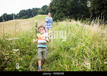 Mother with children picking flowers in the meadow - Stock Photo