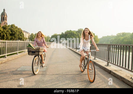 Two women riding bicycle on city bridge - Stock Photo