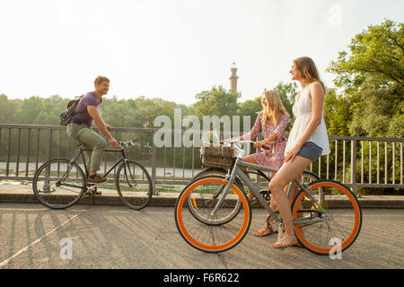 Group of friends riding bicycle on city bridge - Stock Photo