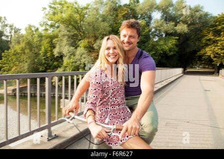 Young couple together on bicycle - Stock Photo