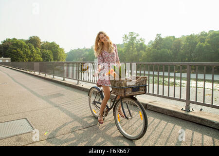 Young woman with bicycle on city bridge - Stock Photo