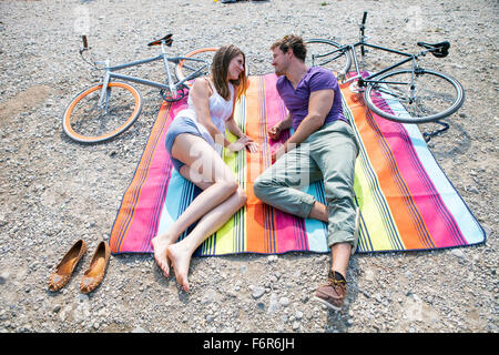 Happy young couple relaxing on the riverbank - Stock Photo