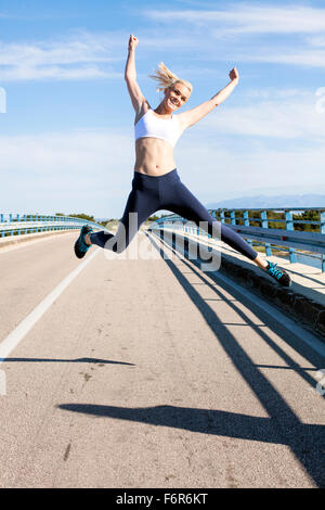 Young woman jumping for joy on the waterfront - Stock Photo