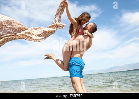 Young man lifting girlfriend on beach - Stock Photo