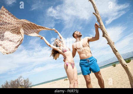 Happy young couple on beach fooling around - Stock Photo