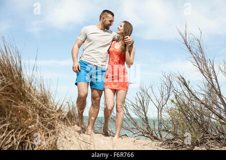 Happy young couple walking in dunes - Stock Photo