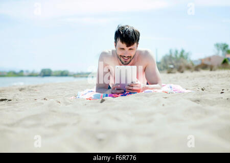 Young man using digital tablet on beach - Stock Photo