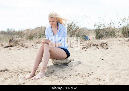 Young woman using digital tablet on beach - Stock Photo