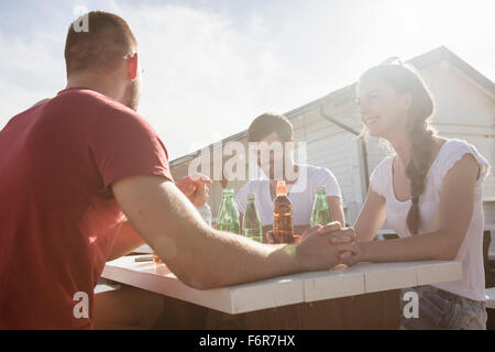 Group of friends celebrating in beach bar - Stock Photo
