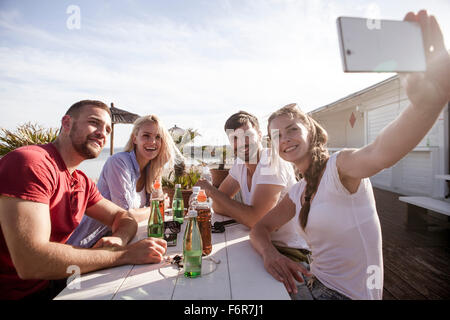 Group of friends taking a self portrait in beach bar - Stock Photo