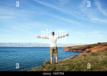 Young man stands on cliff arms outstretched - Stock Photo