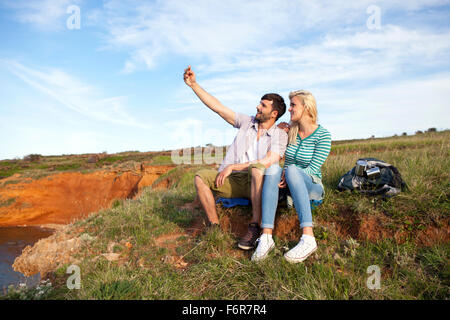 Young couple taking self portrait on cliff - Stock Photo