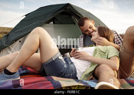 Happy couple at campsite having a cup of coffee - Stock Photo