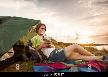 Young woman at campsite drinking cup of coffee - Stock Photo