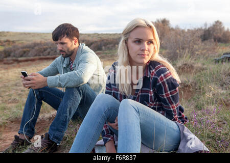 Young couple with MP3 player sitting outdoors - Stock Photo