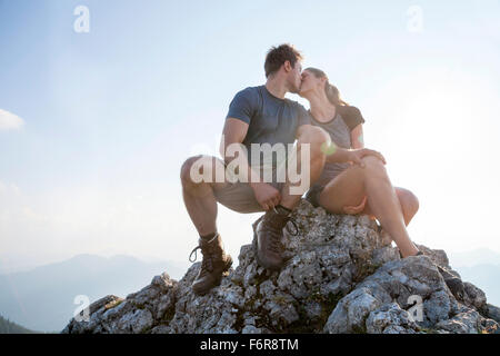 Young couple kissing on mountain peak - Stock Photo