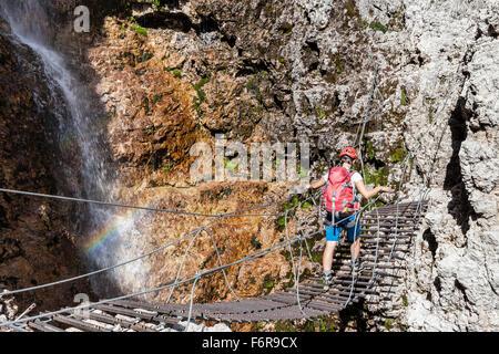 Climbers on suspension bridge, with waterfall, via ferrata Vallonsteig, Piz Boé, Sella, Dolomites, Corvara - Stock Photo