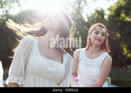 Young woman in hippie style fashion flicking her hair ...
