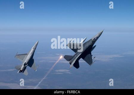 A U.S. Air Force and Royal Netherlands F-16 Fighting Falcon aircraft perform a vertical climb during a training - Stock Photo