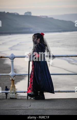 A young girl dressed in  Victorian mourning outfit for The Whitby Goth Weekend standing by railings on the promenade. - Stock Photo