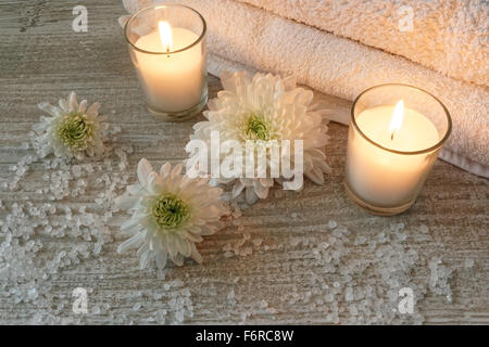 Spa composition with white towels, candles, flowers and bath salt on wooden table - Stock Photo