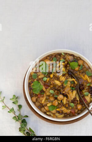 A bowl of harira garnished with fresh cilantro and marjoram is photographed from the top. - Stock Photo