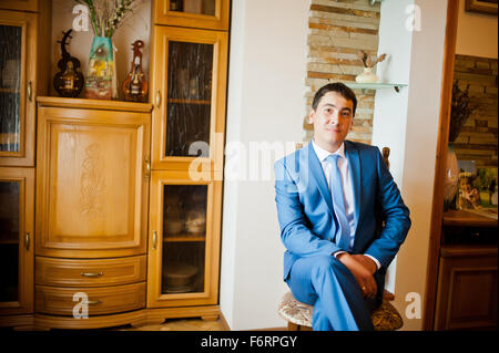 groom  gets dressed in formal wear and blue suit - Stock Photo