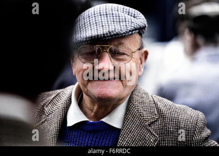 A smiling old gentleman wearing a tweed cloth cap and jacket - Stock Photo