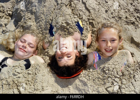 Three young girls buried in the sand at Skegness. Lincolnshire. England. UK. Europe - Stock Photo