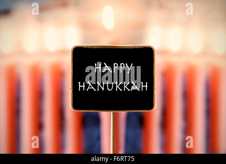 closeup of a chalkboard with text happy Hanukkah and a menorah with nine lit candles in the background - Stock Photo