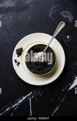 Sturgeon black caviar in can and spoon on black marble background - Stock Photo
