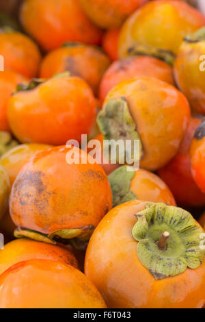 Organic persimmon fruits in pile at local farmers market - Stock Photo