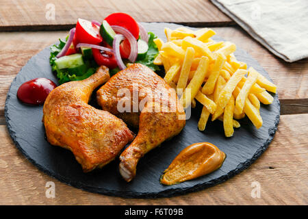 roasted chicken legs with french fries and salad - Stock Photo