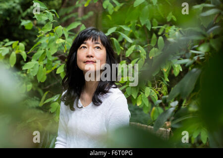 Japanese woman sitting in garden - Stock Photo
