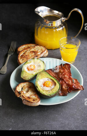 Breakfast with eggs baked in avocado,bacon ,bread toast and orange juice - Stock Photo