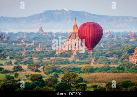 Hot air balloon flying over towers - Stock Photo