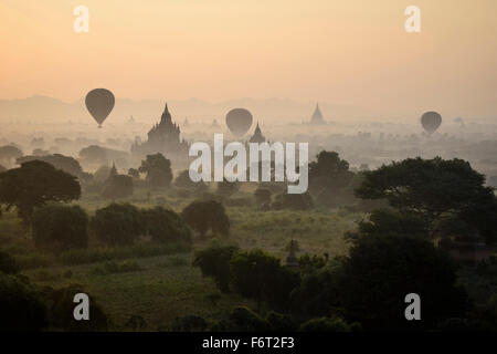 Hot air balloons flying over towers - Stock Photo