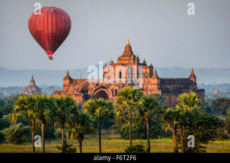 Hot air balloon flying over temple - Stock Photo