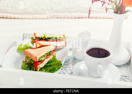breakfast on wooden tray in bed sandwich and coffee - Stock Photo