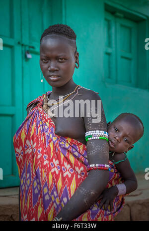 Black woman carrying daughter in sling - Stock Photo