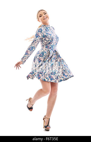 Long-haired blonde girl dancing in a beautiful blue dress.She is wearing a short summer dress with floral print.On - Stock Photo