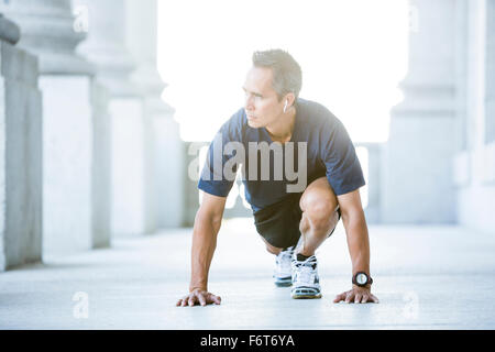 Mixed race man stretching outside courthouse