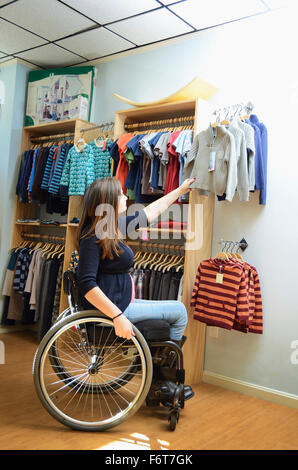 Pregnant paraplegic woman in wheelchair shopping in baby store - Stock Photo