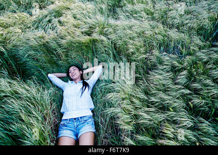 Mixed race woman laying in grass - Stock Photo