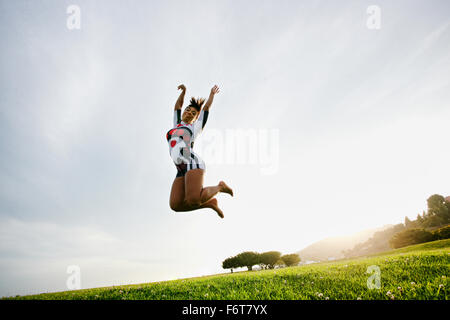 Black woman jumping for joy in field - Stock Photo