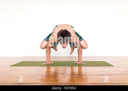Man practicing yoga in studio - Stock Photo