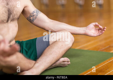 Man practicing yoga in studio - Stock Photo