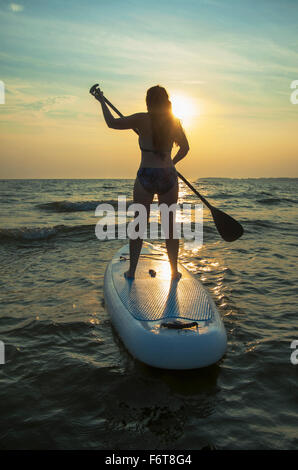 Woman standing on paddleboard in lake - Stock Photo